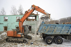 backhoe loading demolition rubble in to a dump truck